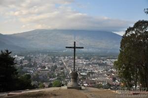Město Antigua, kříž a sopka Agua v pozadí, Guatemala