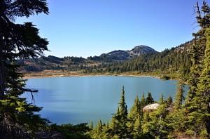 """20/365 Co dělat takhle v sobotu v Kanadě? Tak když nemáte po ruce kolo, tak nejlepší možnost je vzít boty a někam jít. A to přesně jsme udělali i my. Vyrazili jsme k jezeru Rainbow lake, které je asi 8km do kopce směrem od Whistleru. Jezero je hlavním zdrojem vody pro Whistler, tak aspoň víme co tu pijem. Dobrá voda to je. Mimochodem teda, je fakt nezvyk """"protimedvědí pravidlo"""" dělat hluk když někam jdete. Buď by si člověk měl povídat cestou nebo na sebe jinak upozorňovat, dost lidí co jsme potkali neslo na batohu rolničky. Nevěřili byste, jak to může být únavný, snažit se pořád o něčem mluvit :-)"""